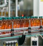 Imagen que refleja un proceso de una fabrica de bebidas, en la cual varias botellas pasan por una banda